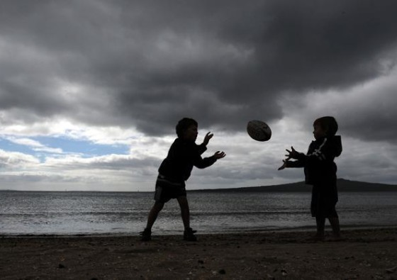 This photo taken on September 3, 2011 shows children playing rugby at Narrow Neck Beach in Devonport near Auckland less than a week before the kickoff of the 2011 Rugby World Cup. The World Cup will be played in New Zealand from September 9 to October 23.  TOPSHOTS  AFP PHOTO / FRANCK FIFE
